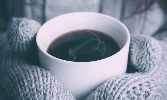 a hot cup of coffee in a white mug held between two grey mittended hands