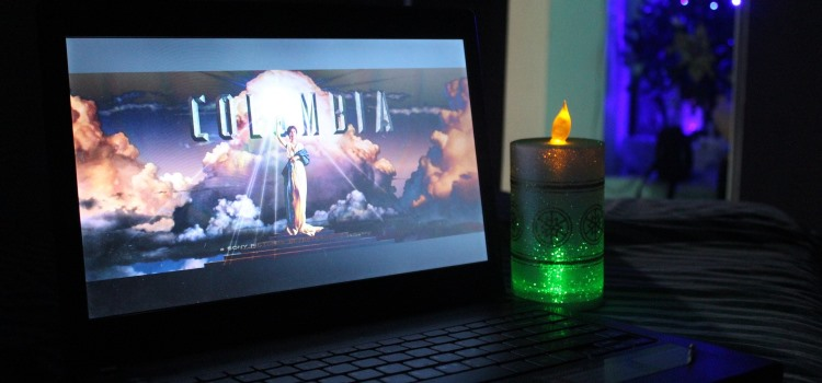 laptop with a Columbia film credit on the screen and a candle beside it