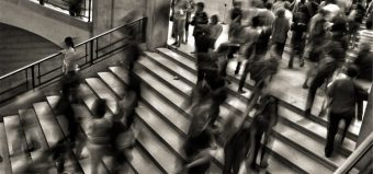 people walking up steps in a busy train station
